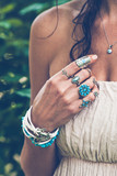 closeup of young woman hand with  lot of boho style jewrly, rings and bracelets outdoor - 208068863