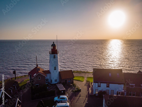 Fotobehang Zee zonsondergang Urk Netherlands a small village alongside the lake ijsselmeer Netherlands with the colorful lighthouse