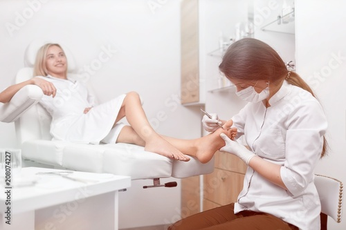 Aluminium Pedicure Podiatrist doctor cleaning foot from callus.