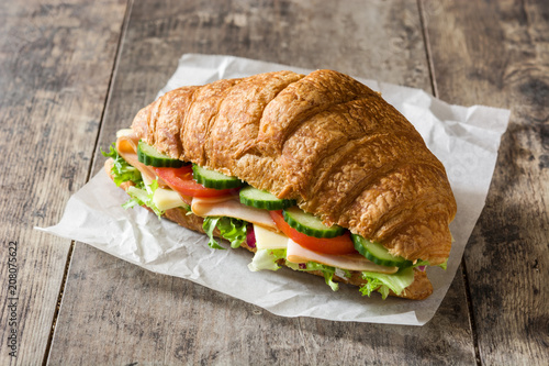 Croissant sandwich with cheese, ham and vegetables on wooden table.