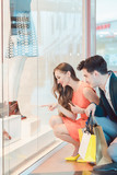 Woman and man looking at fashion shop window wanting to buy a dress - 208079646