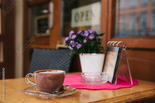 Aluminium Chocolade A cup of hot chocolate or coffee on the table in a cozy outdoor cafe