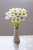 Flower of daisies in a vase in the interior.
