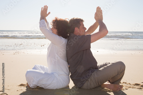 Fotobehang School de yoga relax man and woman make yoga sit on sand beach meditation in sunset vacation