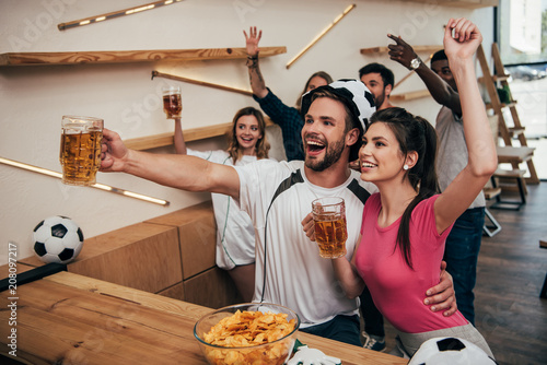 Foto Murales high angle view of happy man in soccer ball hat embracing girlfriend and holding beer while their friends celebrating behind and watching football match at bar