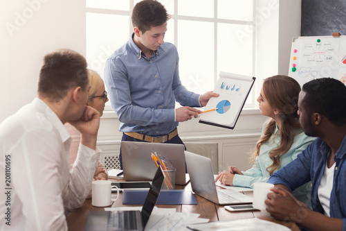 Leinwanddruck Bild Man giving presentation to colleagues in office