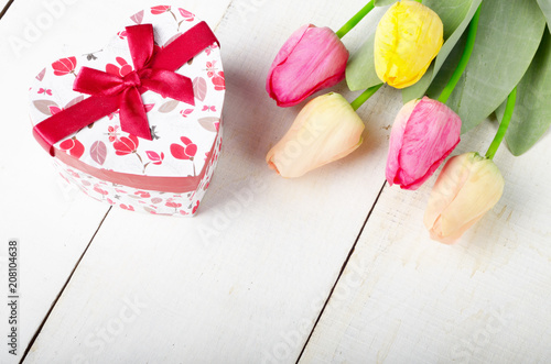 High angle shot of pink rosy and yellow Spring tulip flowers and gift box on white wooden table