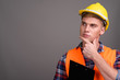 Young handsome man construction worker against gray background