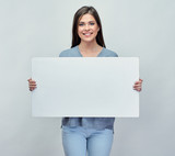 Smiling woman holding white advertising board with empty copy sp