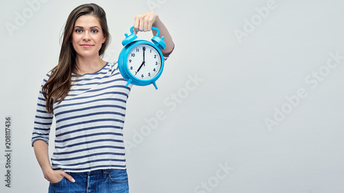 Young woman wearing striped shirt holding big alarm clock.