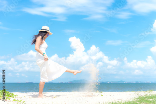 Smiling asian woman white wearing fashion summer walking on the sandy ocean beach.  Woman enjoy and relax vacation. Lifestyle and Travel Concept.