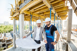 Engineer standing with builder supervising the construction process with house drawings on the structure outdoors - 208119220