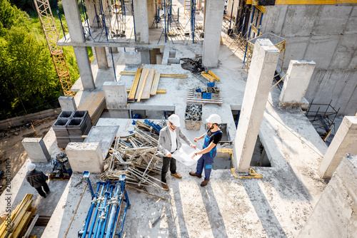 Poster Top view on the construction site of residential buildings during the construction process with two workers standing with drawings