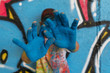 Teen smiling with hands in front of his face, is painted blue with a graffiti