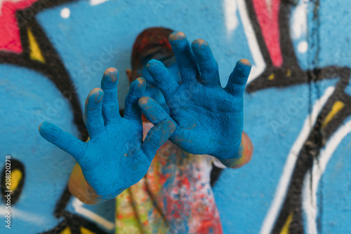 Teen smiling with hands in front of his face, is painted blue with a graffiti - 208120278