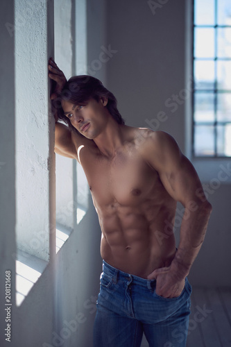 Leinwanddruck Bild Shirtless handsome male with a perfect muscular body leaning on a wall in the studio, looking at a window.