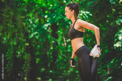 Leinwanddruck Bild Beautiful sportswoman stretching leg in the park. Morning exercise concept.