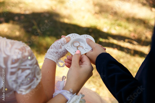 Fototapeta Wedding ceremony. Guests holding ring box with wedding rings for bride and groom
