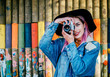 Leinwanddruck Bild - Image of a young female photographer standing in front of colorful wall.