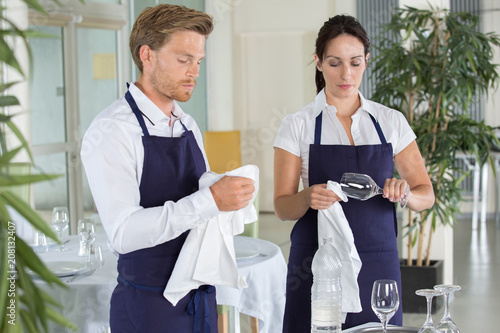waitress and waiter cleaning glasses in a restaurant