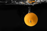 Photo of an orange falling into the water creating splashes
