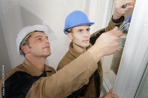Workmen fitting new window - 208139448