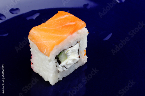 Aluminium Sushi bar One roll of Philadelphia sushi on a dark blue background. Drops on the background. A photo of Japanese food close-up.