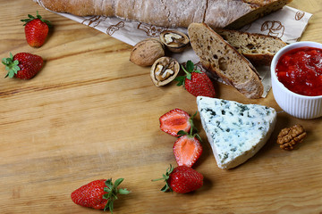 buttery, salty blue cheese with strawberry sauce, whole grain bread, walnut on a wooden background. Top view with copy space. set