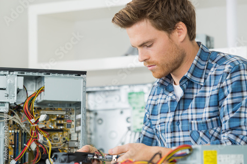 handsome computer engineer repairing a faulty pc