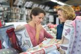 friends customers choosing carpet in housewares hypermarket - 208149038