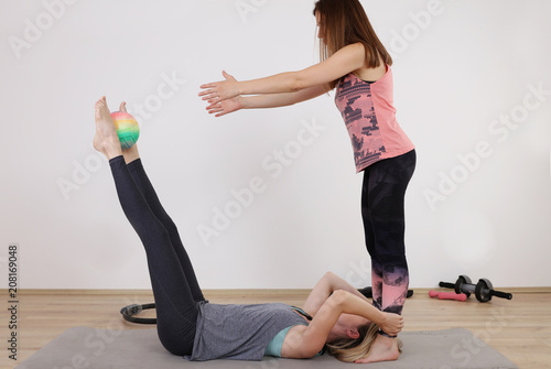 Poster Partner workout. Two female friends doing abs exercises at gym