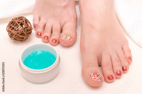 Aluminium Pedicure Beautiful woman feet and moisturizing cream on white background. Care of female legs concept. Spa salon.