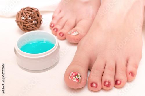 Fotobehang Pedicure Beautiful woman feet and moisturizing cream on white background. Care of female legs concept. Spa salon.