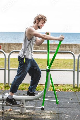 Poster Active man exercising on elliptical trainer.