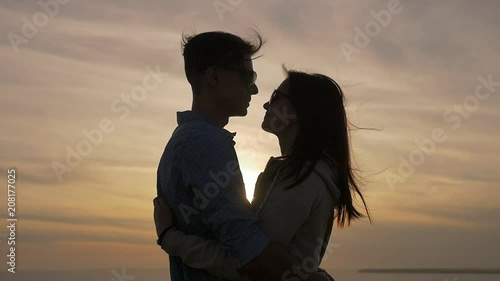 Profile of a young woman embracing her enchanted sweetheart on the Black Sea shore at wonderful sunset with a shining sun path in summer