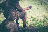 Young male hiker with backpack relaxing on top of a mountain - scenery from vacation - photo with space for your montage.
