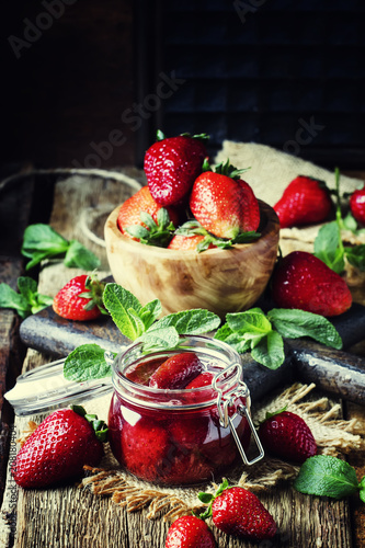 Strawberry confiture with whole berries, vintage wooden background, selective focus © 5ph