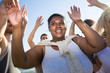 Cheerful African-American woman smiling and dancing among friends while having fun during multiracial beach party.