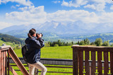 Tourist in the mountains photographing beautiful views.