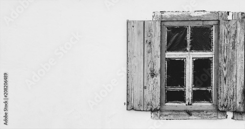 white wall of a village house with an old wooden window, black and white photo - 208206489