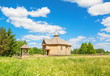 Small wooden old rural church in the field with dandelions