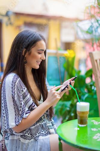Attraktive, junge Hipster Frau benutzt ihr Mobiltelefon in einem Cafe in der Stadt