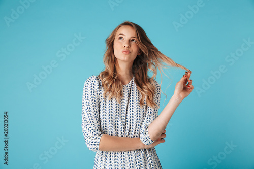 Pensive smiling blonde woman in dress playing with her hair