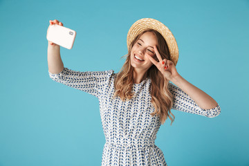 Smiling woman in dress and hat making selfie on smartphone