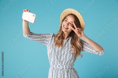 Leinwanddruck Bild Smiling woman in dress and hat making selfie on smartphone