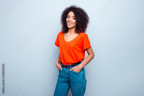 Leinwanddruck Bild Portrait of joyful cute woman with modern hairdo in bright t-shirt jeans holding two hands in pockets isolated on grey background
