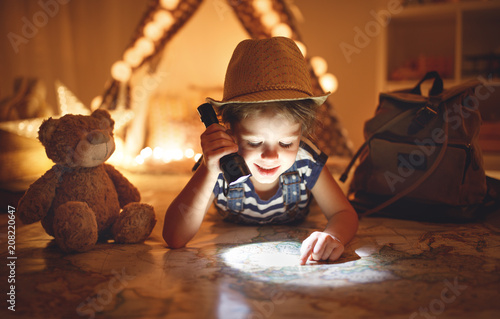 funny child girl tourist with flashlight and world map and backpack