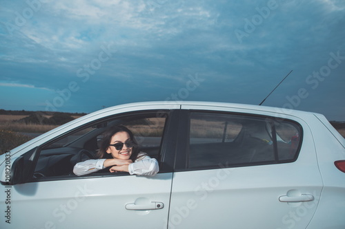 Wonderful landscape. Portrait of cheerful girl is enjoying view from the window of her personal transport. She is smiling