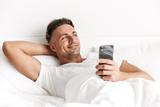 Smiling man holding mobile phone - 208224691
