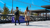 Two women in stylish spring coats and backpacks walk on the city embankment of Kazan. bottom rear view